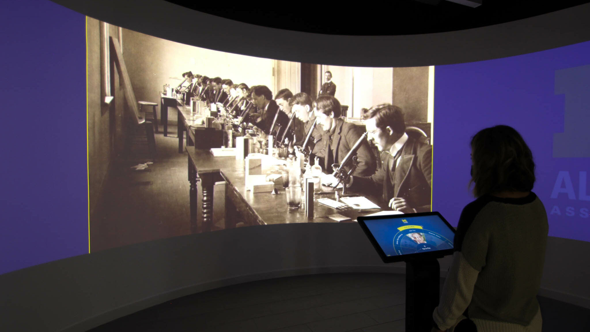 A visitor watches historical imagery in the University of Michigan Alumni Center Immersion Room